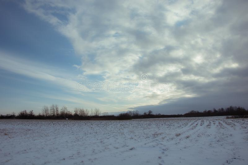 Sun behind gray cloud and snow-covered field. Winter view royalty free stock photos