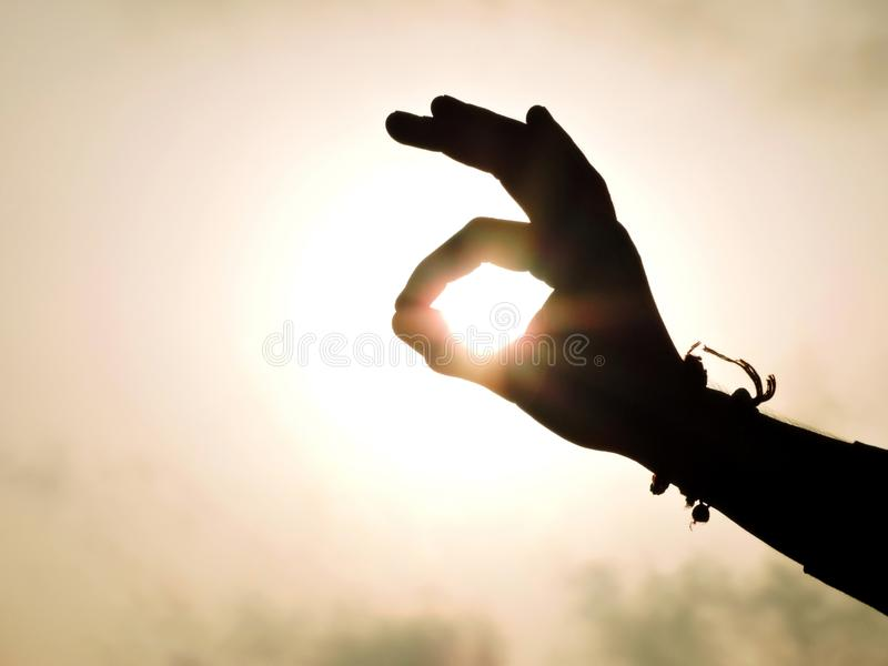 Sun behind the hand stock image