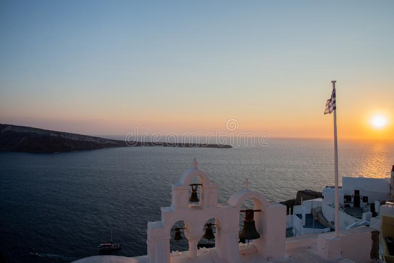 The sunset of Santorini volcanic island of the Aegean Sea in Greece, offers a fantastic panorama of the caldera. The sun behind the horizon line, with the stock image