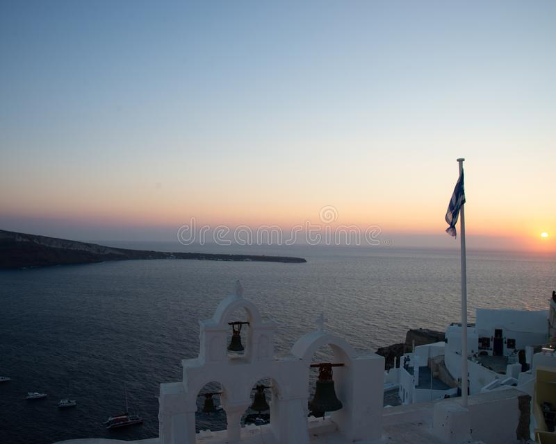 The sunset of Santorini volcanic island of the Aegean Sea in Greece, offers a fantastic panorama of the caldera. The sun behind the horizon line, with the stock photo