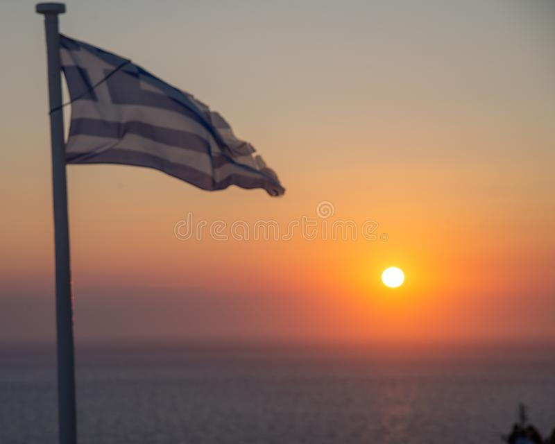 The sunset of Santorini volcanic island of the Aegean Sea in Greece. The sun behind the horizon line, with a Greek flag foreground. The most romantic place in royalty free stock images