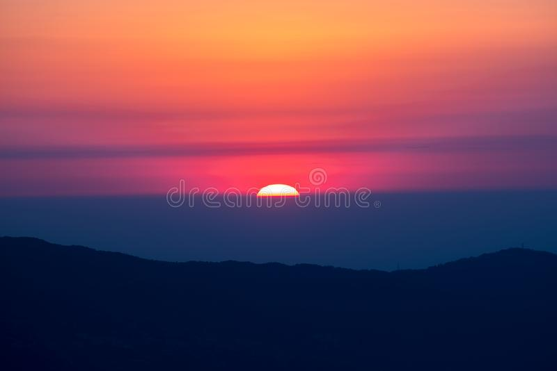 Sun behind mountain layer during chage of light. From nuture stock photo