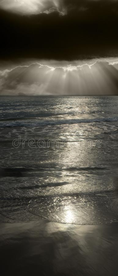 Sun rising over the ocean. The sun behind stormy clouds, rising over the waves of the ocean breaking on the beach royalty free stock image
