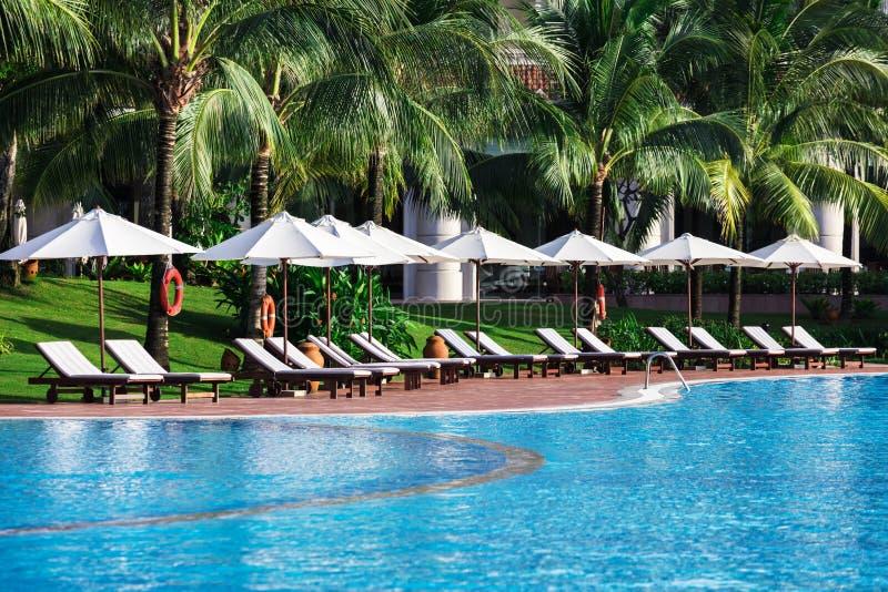 Sun-Betten auf nahem Pool stockfotos