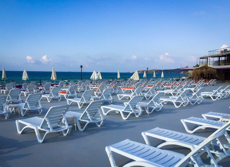 Sun-Betten am leeren Strand lizenzfreie stockbilder