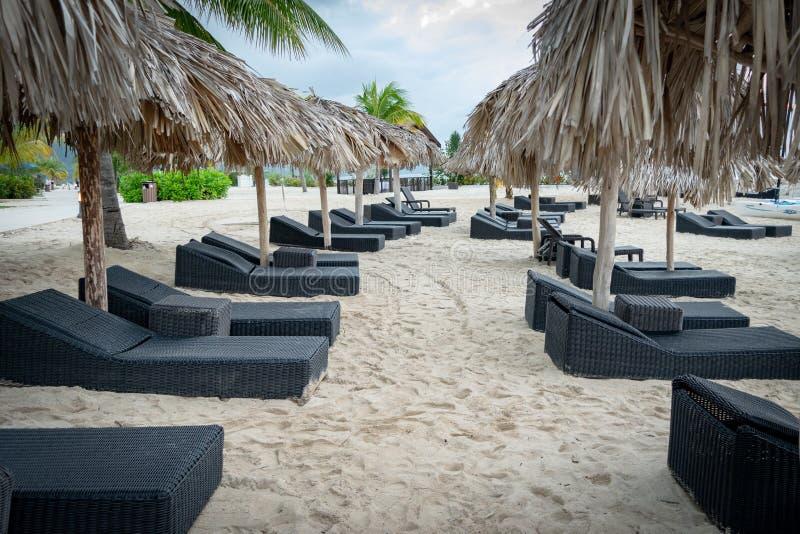 Sun-Bettklubsessel und -stroh decken Dachregenschirme auf tropischem Strand mit Stroh stockfotografie
