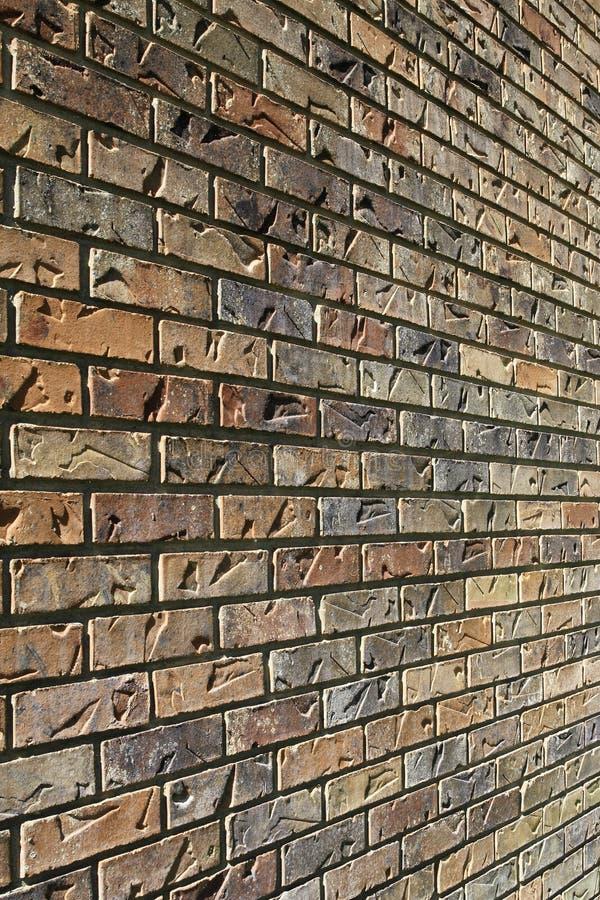 Sun blickt weg von einer Backsteinmauer mit den Eindrücken flüchtig, die ihm Beschaffenheitshintergrund geben stockfotos