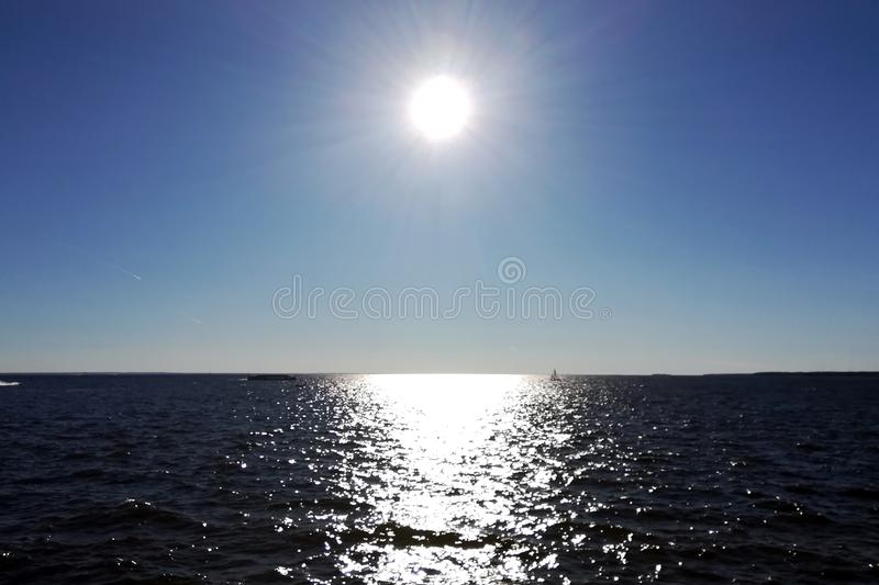 The Sun in the blue sky and the sun glare on the water stock photo