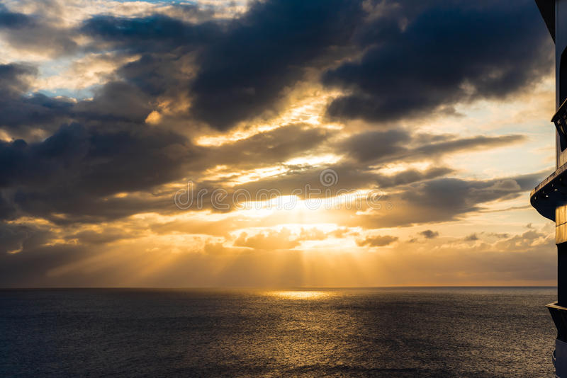 Sun breaking through at sunset with reflection on the on the ocean horizon view from ship royalty free stock image