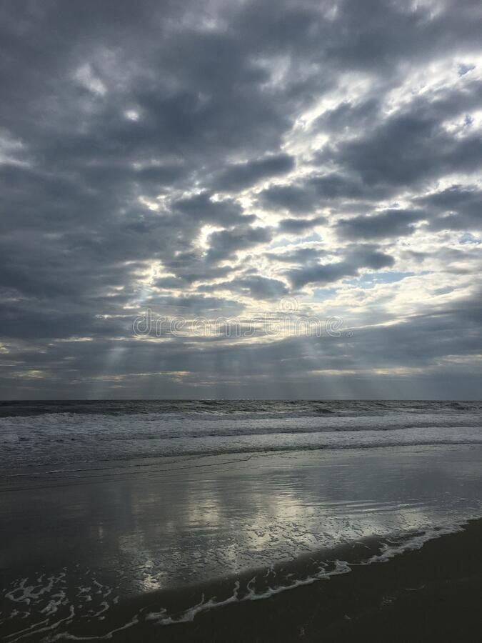 Sun breaks through the clouds on a beach. The sun breaks through the clouds onto the water at the beach on a Sunday creating royalty free stock image