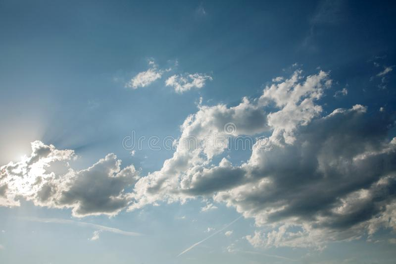 The sun breaks through the cumulus clouds. On the blue sky royalty free stock photography