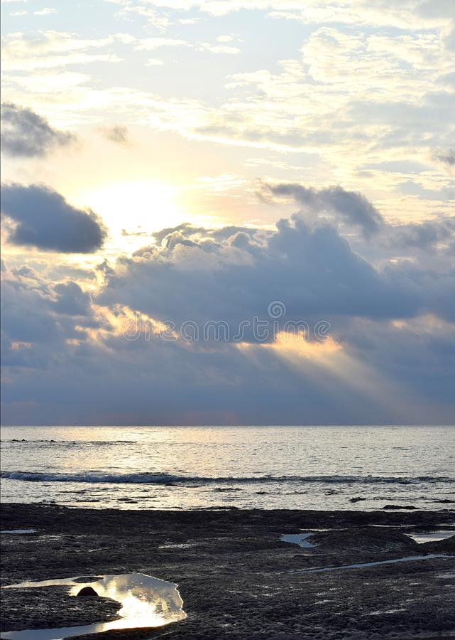 Sun with Bright, Golden Yellow and Orange Aura, behind Dark Clouds and Sunlight falling on Calm Sea Water through Clouds in Sky stock photography