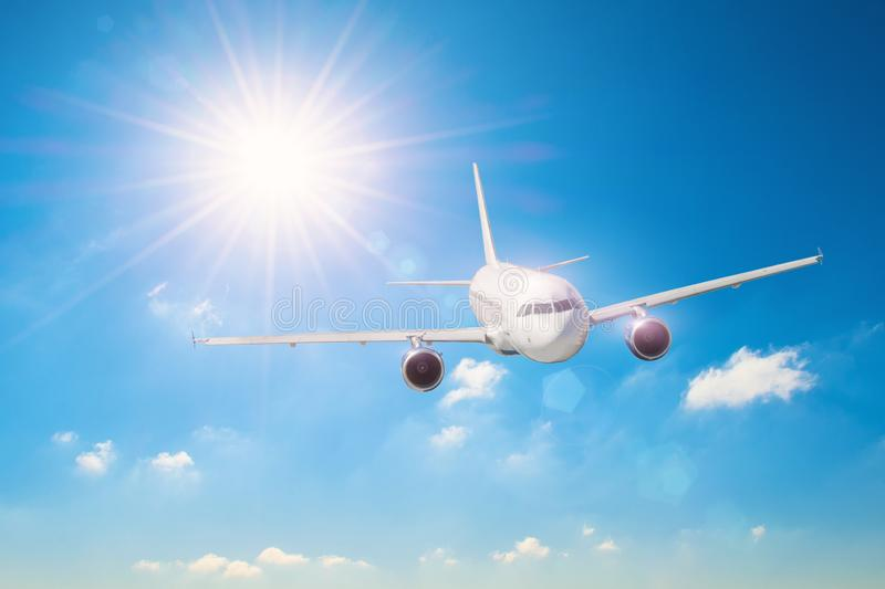 Sun with bright rays in the blue sky with white light clouds, flying airplane traveling on vacation.  stock images