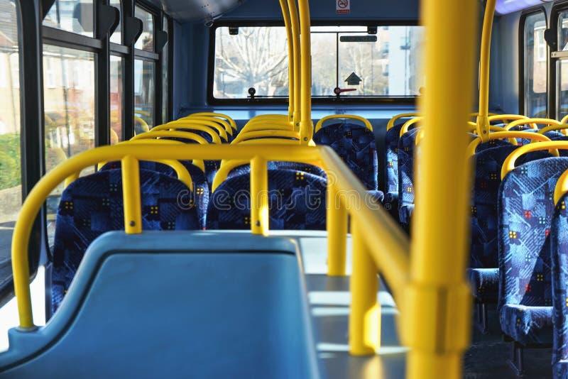 Sun brilla en el interior vacío del autobús del autobús de dos pisos de Londres, de carriles que se sostienen amarillos y de asie foto de archivo libre de regalías