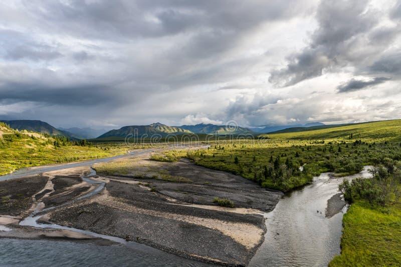Sun brilla a través de las nubes sobre los planos de la tundra y de la grava imagen de archivo libre de regalías