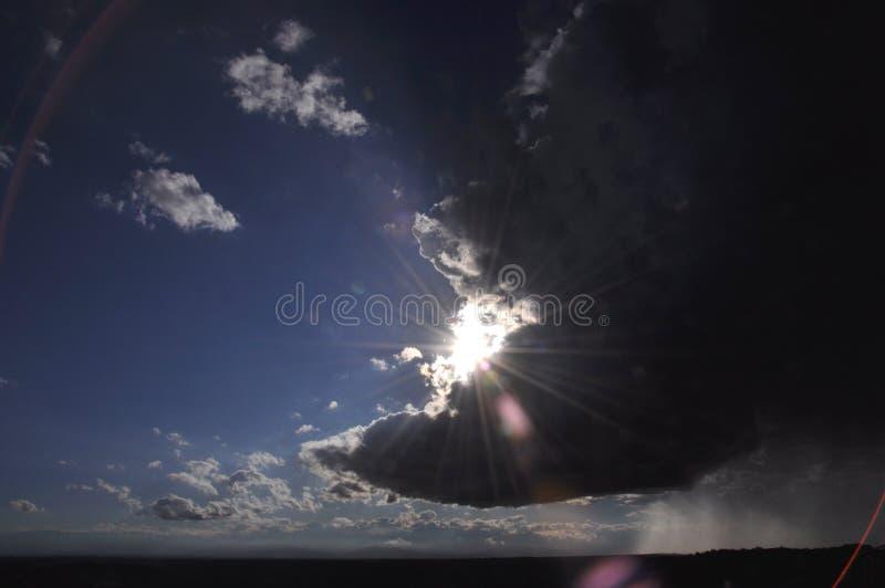 Sun brillant par des nuages de tempête photographie stock
