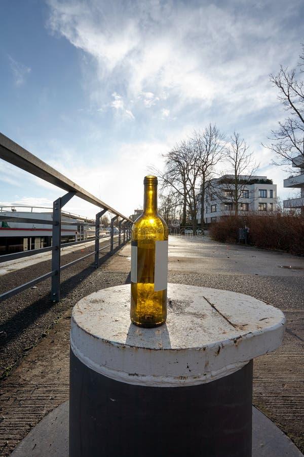 Sun brillant par une bouteille de vin, se tenant sur une borne, sur un dock, un matin doux d'hiver photo libre de droits