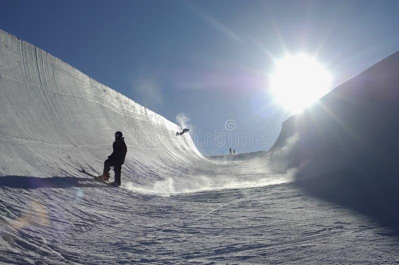 Sun brillant sur des personnes faisant du surf des neiges en parc photos stock