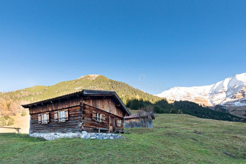 Sun burned timber chalet hut on austrian mountains stock photos