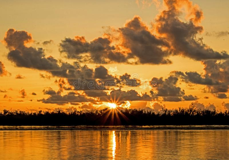 Sun Bursts Above The Horizon Across The Caribbean Tidal Pool. The rising sun bursts between the horizon and clouds across the tidal pool in tropical Cayo Coco royalty free stock photography