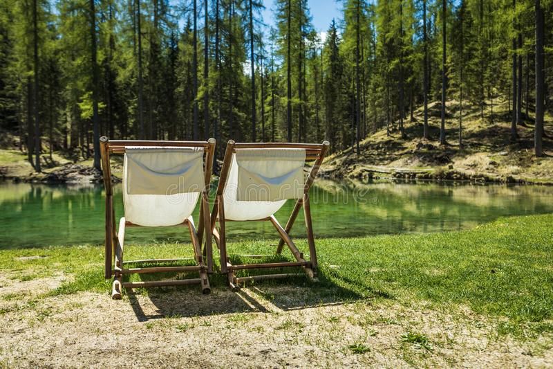 Sun chairs in Lago Ghedina, an alpine lake in Cortina D`Ampezzo, Dolomites, Italy stock photos