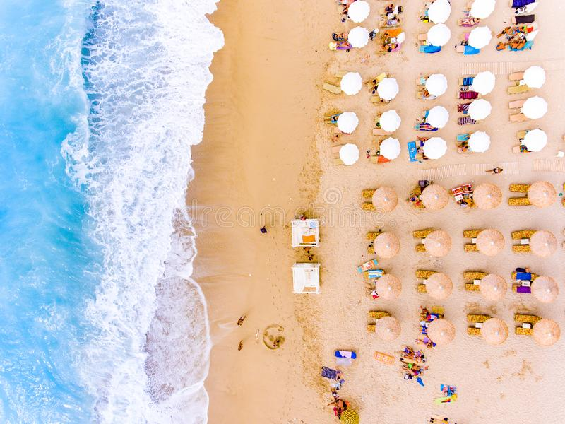 Sun chairs and umbrellas bird`s eye view on sand beach in Greece stock photography