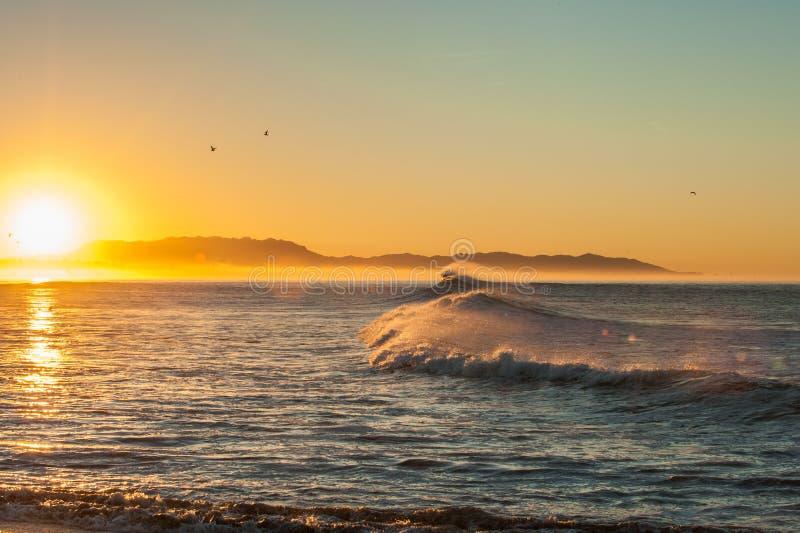 Sun che aumenta dietro le onde soffiate vento di terra immagine stock libera da diritti