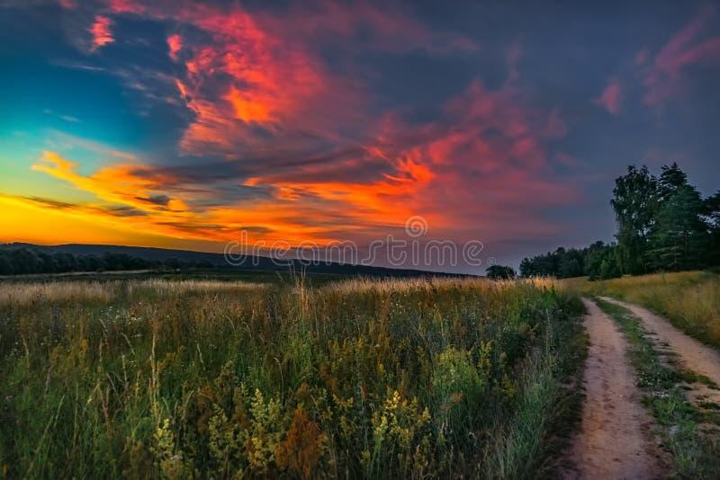 Sun che mette sopra un sentiero per pedoni rurale nella valle fotografie stock libere da diritti