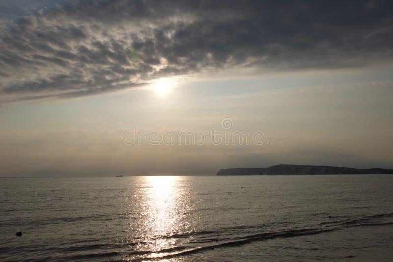 Sun che riflette fuori dall'acqua uguagliante sulla costa sud dell'Inghilterra fotografia stock