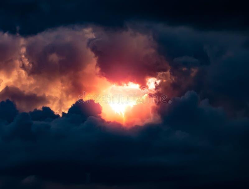 Sun che splende attraverso un cielo scuro drammatico immagini stock libere da diritti