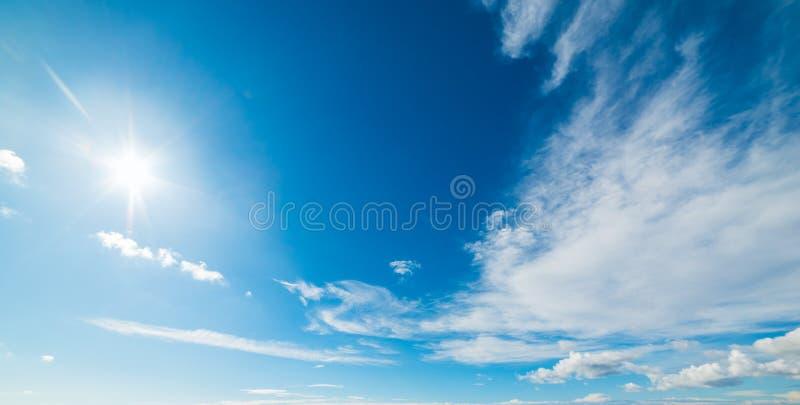 Sun che splende in un cielo blu con le nuvole immagine stock
