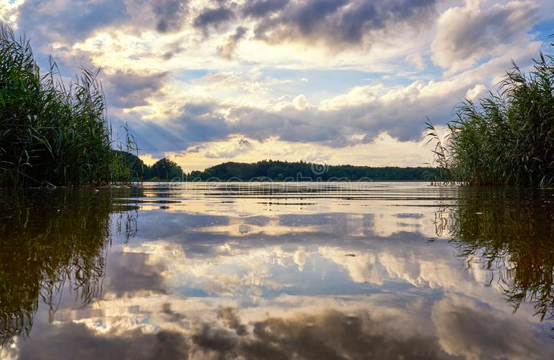 Sun and clouds in the dramatic sky are reflected in the lake. Natural background with clouds and water stock image