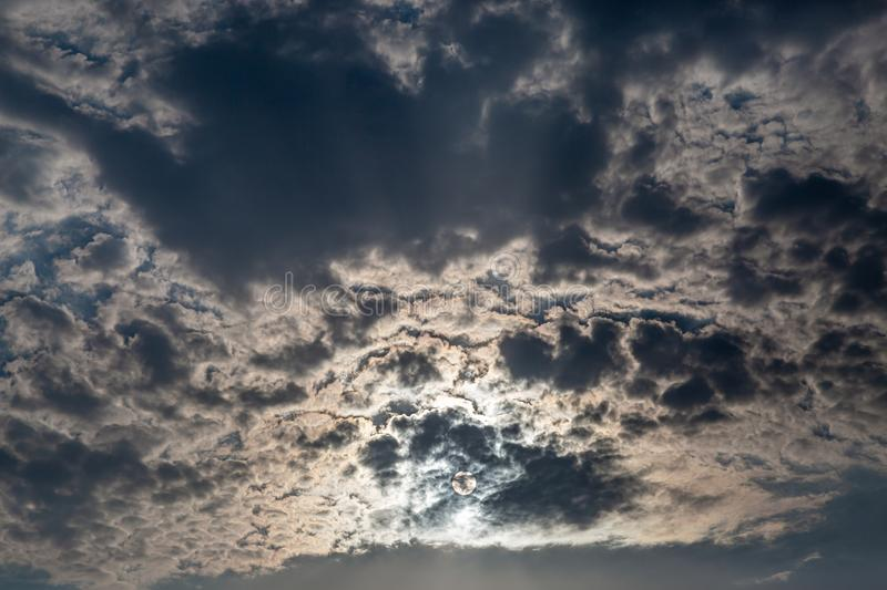Sun and Clouds. Looking up at white and dark clouds obscuring the sun royalty free stock image