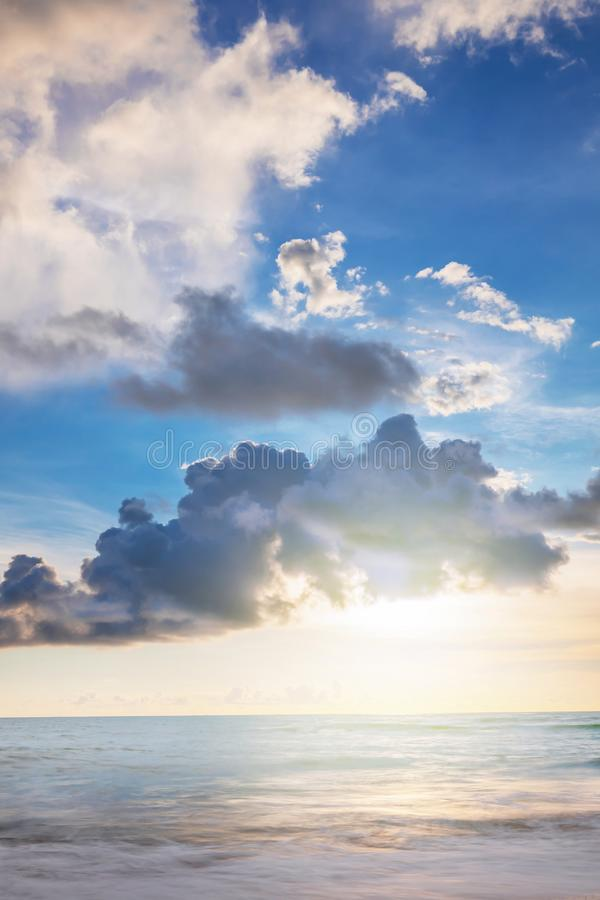 The sun in clouds. the sun shines through the dark gray clouds, the light is reflected in the calm blue sea, a beautiful landscape royalty free stock images