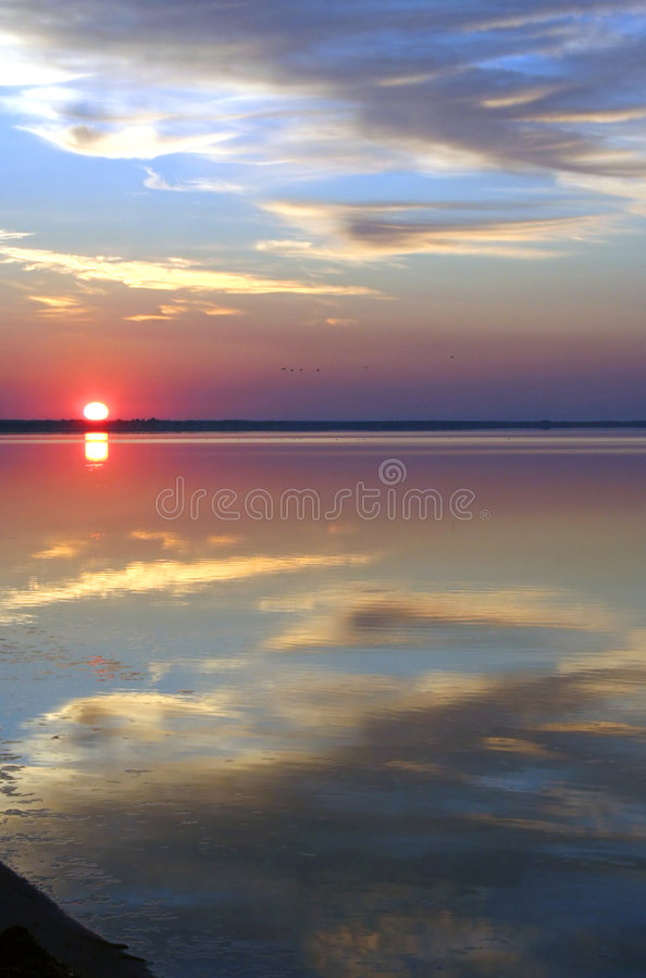 The sun, clouds and water stock image