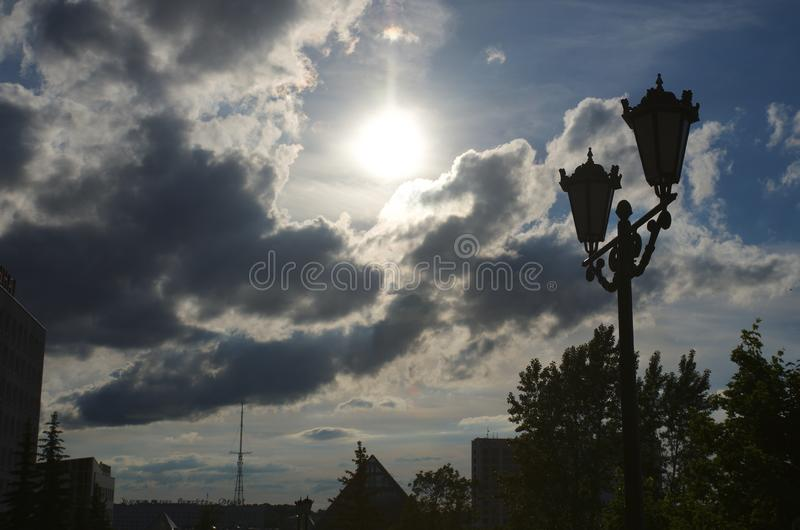 Sun at cloudy sky, cumulus clouds lights in sun rays, street light post at foreground royalty free stock images