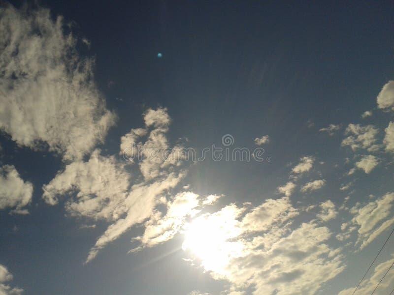 Sun a couvert par les nuages blancs en ciel images libres de droits