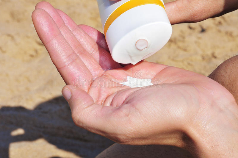 Sun cream. Someone applying sun cream in the beach royalty free stock images