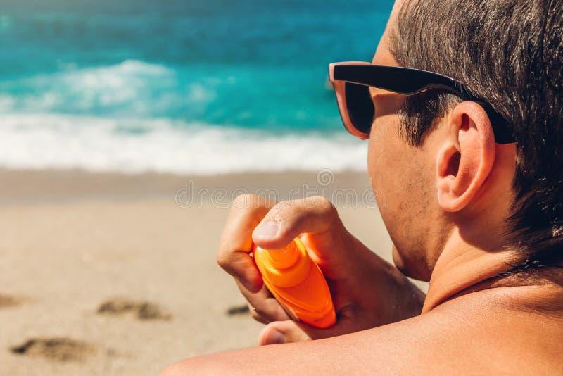 Sun cream protection. Man sprays sun cream on his shoulder. Skin care concept. Healthy skin on vacation. stock photos