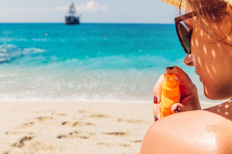 Sun cream protection. Woman sprays sun cream on shoulder. Skin care concept. Healthy skin on vacation. royalty free stock photos