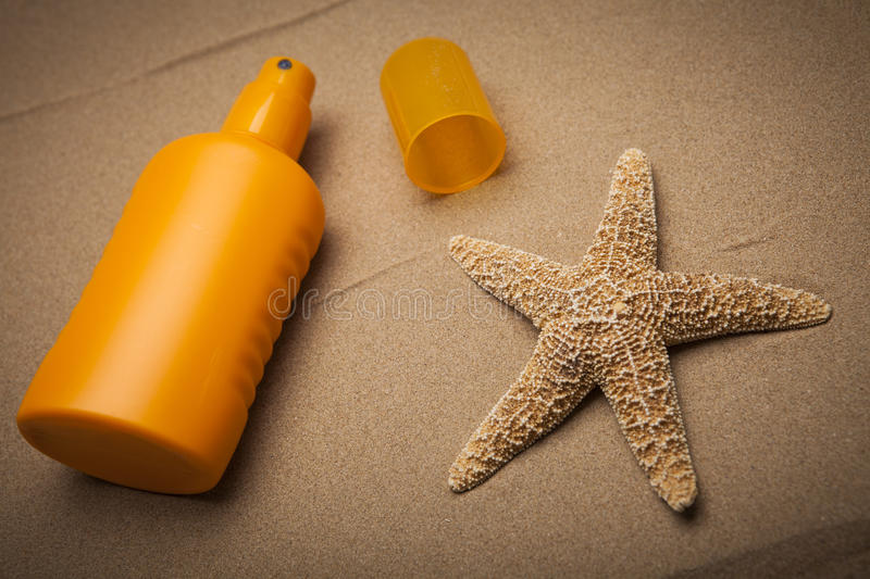 Sun cream. And starfish on the sand royalty free stock photography