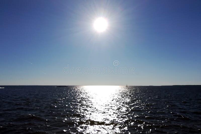 The Sun in de blauwe hemel en de zonglans op het water stock foto