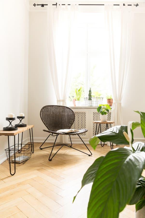 Sun, der in einen Rauminnenraum mit einem Rattan scheinen und Metall sitzen a vor lizenzfreie stockbilder