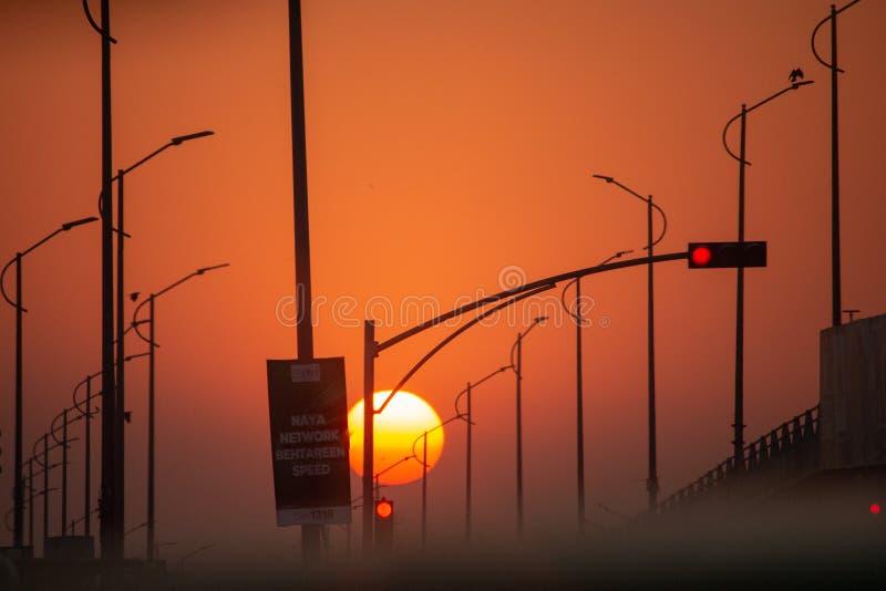 Sun, der mitten in einer leeren Straße einstellt stockbild