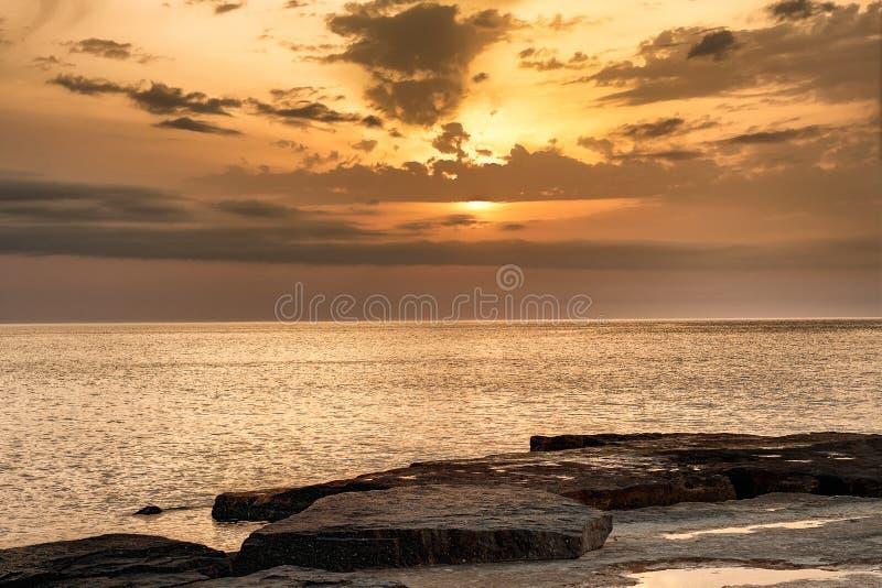 Sun, der unten über das Wasser glüht auf das Ufer hinausgeht stockfoto