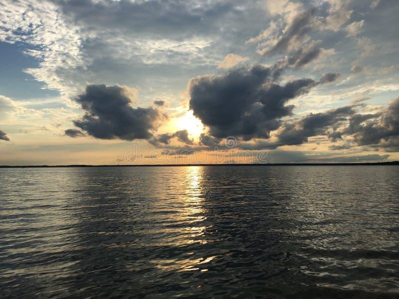 The Sun derrière les nuages au-dessus du lac photos libres de droits
