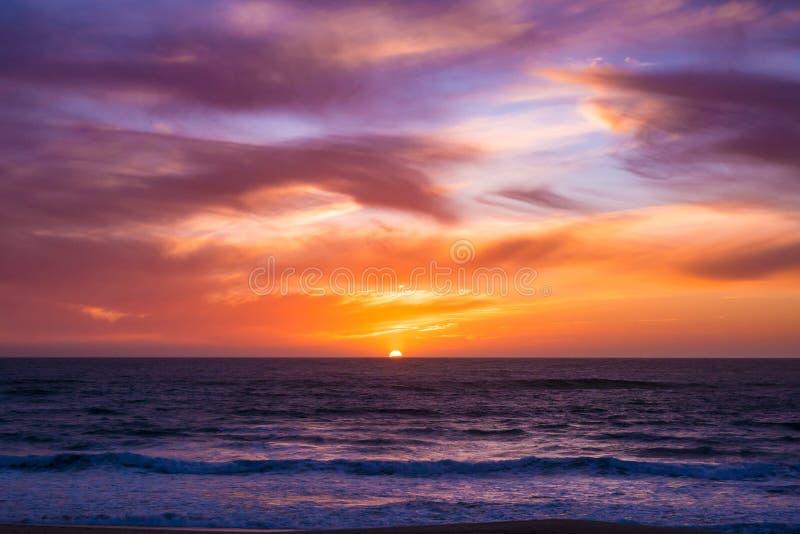 Sun desaparece abaixo do horizonte sobre o oceano após o por do sol espetacular com céu vívido imagem de stock