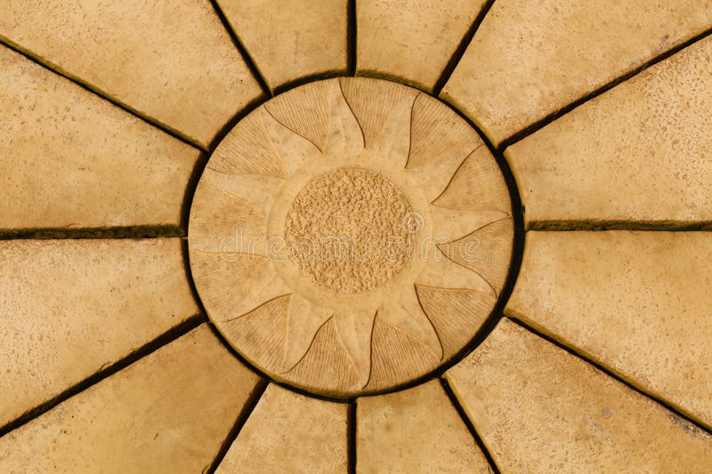 Sun design on golden coloured paving stone star pattern. Backgr royalty free stock photography