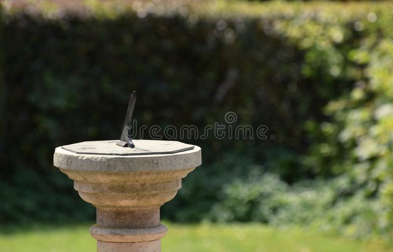 Sun dial in a Summer garden. A traditional stone sundial in an English country garden in Summer royalty free stock image