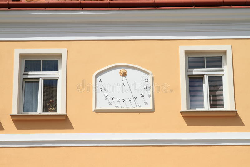 Sun-dial. On wall with windows around in Telc (Czech Republic royalty free stock photography